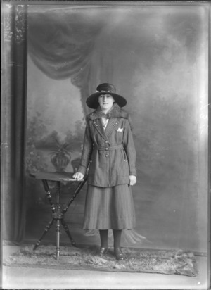 Studio portrait of an unidentified woman leaning on a table, wearing a hat and pinned striped suit and a fur capelet, probably Christchurch district