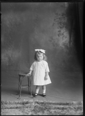 Studio portrait of an unidentified girl wearing a white dress, with a big ribbon bow in her hair, showing the girl standing next to a stool resting her right hand on the stool, possibly Christchurch district