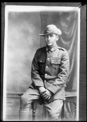 Studio portrait of unidentified young soldier sitting against a table wearing slouch hat, and with silver fern badges on collars, Christchurch