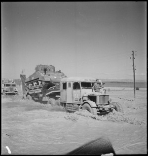 Tank transporter carrying Sherman tank over flooded stream, Tunisia - Photograph taken by M D Elias