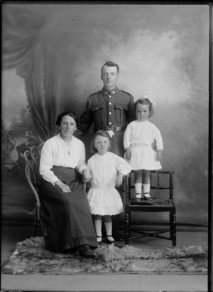 Studio unidentified family portrait, a World War I soldier with [Tui or Huia?] collar badges and wife with portrait necklace, alongside young daughters, Christchurch