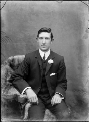Studio portrait of unidentified man, with a flower on his lapel, probably Christchurch district
