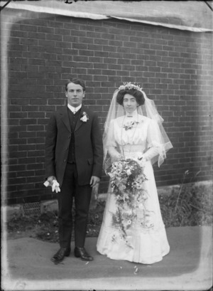 Unidentified wedding couple, outside a brick building, probably Christchurch district