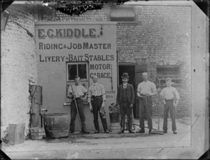Five men standing in front of the business premises of E G Kiddle, Riding and Jobmaster, Livery and Bait Stables, England