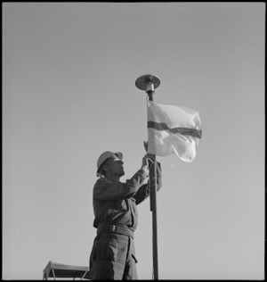 C L Devereaux hoisting the Signals flag in the Western Desert, World War II - Photograph taken by H Paton