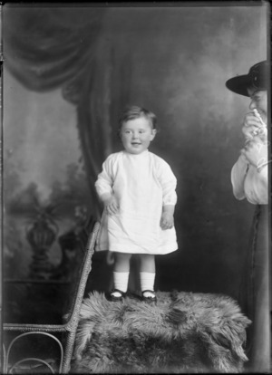 Studio portrait of young girl standing on a fur rug, with her mother alongside (partially obscured), Christchurch