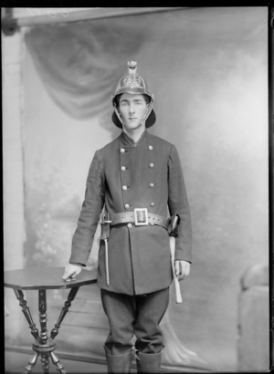 Studio portrait of an unidentified man wearing a fireman's suit with helmet, tool belt with spike tool, axe, possibly Christchurch district