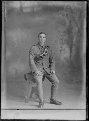 Studio portrait of an unidentified World War I soldier with bandolier ammunition belt over left shoulder, collar badges and stirrups [Mounted Rifles?], Christchurch