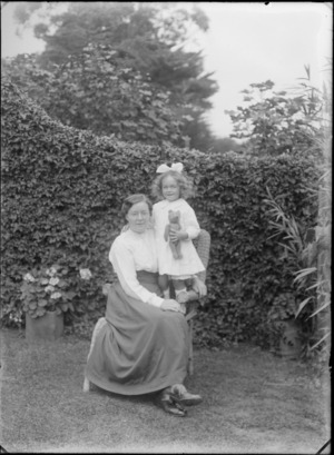 Outdoors on grass in front of a hedge, an unidentified family portrait of a mother with glasses sitting with her young daughters with hair bow standing holding a teddy bear, probably Christchurch region