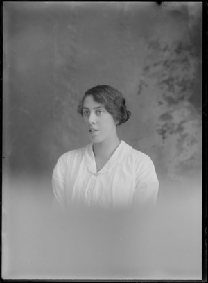 Studio upper torso portrait of an unidentified young woman in a large collar buttoned shirt with bar brooch and necklace, Christchurch