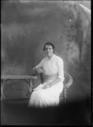Studio portrait of unidentified woman, wearing a chain bracelet and holding a book, probably Christchurch district