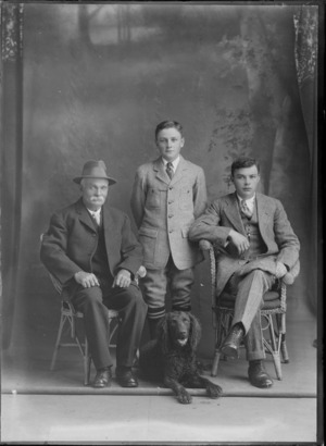 Studio portrait of an unidentified elderly man with a moustache, and two youths, with a dog, probably Christchurch district