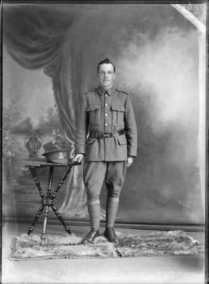 Studio portrait of unidentified World War I soldier standing with his hat on a table, with Liverpool collar and hat badges [Rifle Brigade Reinforcements?], Christchurch