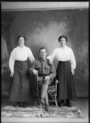 Studio portrait of unidentified World War I soldier with 'Liverpool' collar badges, sitting between two women with pearl necklace and bar brooch, Christchurch