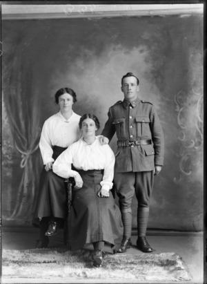 Studio portrait of unidentified World War I soldier with 'Liverpool' collar badges, standing beside two women with necklace and bar brooch, Christchurch