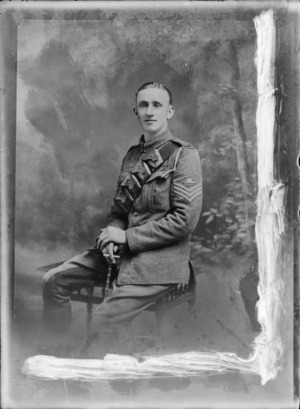 Studio portrait of unidentified World War I soldier with bandolier ammunition belt, artillery sleeve badge and white shoulder pocket cord, sitting with cigarette and swagger stick in hand, location unknown