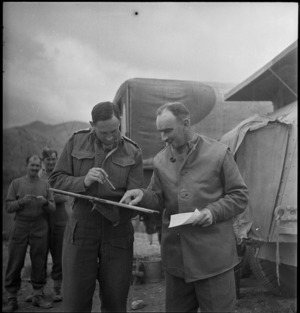 Brigadier Weir studies report handed him by Captain Sidey during initial action in Italy, World War II - Photograph taken by George Kaye