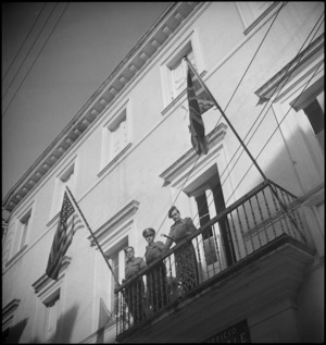 NZ soldier stands with American and British soldiers on a balcony of a building in Atessa, Italy, World War II - Photograph taken by George Kaye