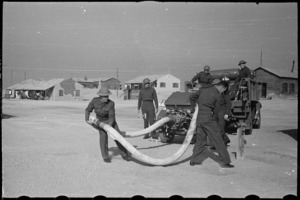 Members of NZ Maadi Camp Fire Unit coupling up suction hose during training, Egypt, World War II - Photograph taken by George Bull