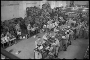 Chief NZ Post Office Cairo showing the checking of addresses and sorting of parcels for NZ Division, World War II - Photograph taken by George Bull