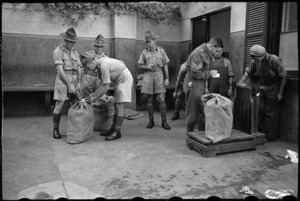 Sergeant D W Lake records the weight of consignment of NZEF Times to be transported to NZ troops - Photograph taken by George Bull