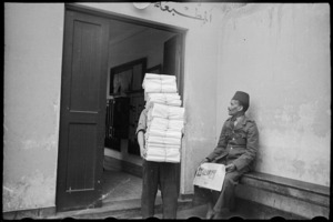 Porter carries bundles of the NZEF Times to truck for transportation, Egypt, World War II - Photograph taken by George Bull