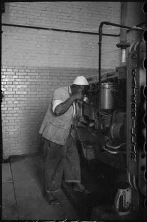 Local Egyptian attending to the diesel engine generating power for Maadi Camp, Egypt - Photograph taken by George Bull