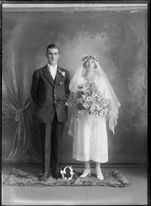 Studio portrait of unidentified wedding couple, groom in a stiff wing shirt collar, white bow tie and rose buttonhole, bride with long veil and pearl necklace holding flowers, with lucky horse shoe between them, Christchurch