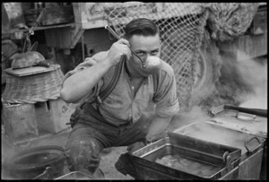 W T Keighley tastes part of the Christmas dinner for a section of NZ Division in Italy, World War II - Photograph taken by George Kaye