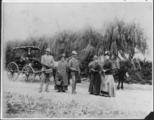 Group of people standing on a road by horses and a carriage