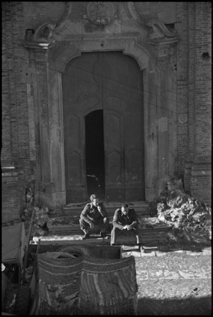 Two soldiers resting outside village church, Italy, World War II - Photograph taken by George Kaye