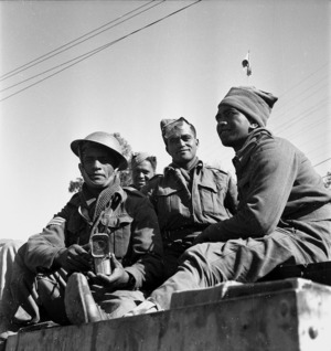 Paton, H, fl 1942 (Photographer) : Four unidentified soldiers of the Maori Battalion share a tin of bully beef in Tripoli, Libya