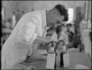 Removing tubes from bottles of donated blood and preliminary sealing at Maadi Camp Hospital, World War II - Photograph taken by G Bull