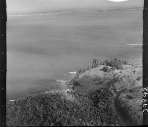 The Snow Rainger property on a headland with buildings, bush and steep cliffs at Hatfield's Beach settlement, North Auckland, with the Hibiscus Coastal Highway in the foreground