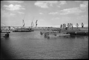 NZ engineers position box girder in the rebuilding of a pontoon bridge across Suez Canal, World War II - Photograph taken by George Kaye