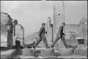 Two Kiwi soldiers negotiating stepping stones in a street in Pompei, Italy, World War II - Photograph taken by George Kaye