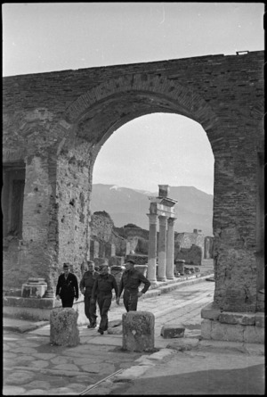 New Zealand soldiers with a guide walk beneath archway in the Via Fortuna, Pompei, Italy, World War II - Photograph taken by George Kaye