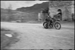 Dispatch rider B J Beasley, Maori Battalion, passes at speed on 5th Army Front, Italy, World War II - Photograph taken by George Kaye