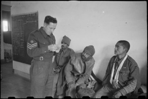 British staff sergeant checks medical cards for Indian army patients at English hospital in Caserta, Italy, World War II - Photograph taken by George Bull