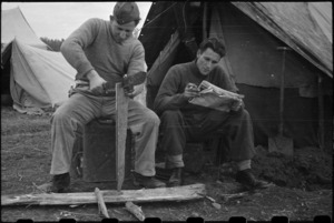 Private O J Spinetto cuts firewood while Corporal H Kingston reads at the NZ LOB Camp, Italy, World War II - Photograph taken by George Bull