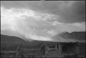 Sunlight breaking through clouds over Cassino lightens up smoke screen laid down following bombing, Italy, World War II - Photograph taken by George Kaye
