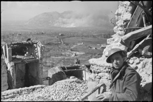 Photographer M D Elias observing the results of the bombing raid on Cassino, Italy, World War II - Photograph taken by George Kaye
