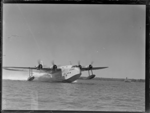 Short Empire flying boat 'Aotearoa' ZK-AMA, skimming across water on an unidentified harbour