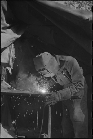 H P Partington does an electric welding job at NZ Divisional Field Workshops, Cassino Front, World War II - Photograph taken by George Kaye