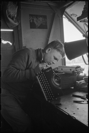 J E Thompson adjusts a typewriter at NZ Divisional Field Workshops, Italian Front, World War II - Photograph taken by George Kaye