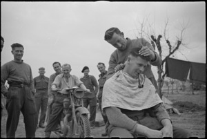 NZ Infantry soldier has a haircut behind the lines on the Cassino Front, Italy, World War II - Photograph taken by George Kaye