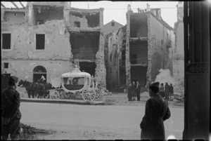 Elaborate hearse in front of damaged building in Italian town in the Volturno Valley, World War II - Photograph taken by George Kaye