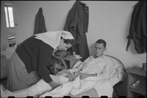 Sister E A Worsp bandaging Private J Donnelly at 2 NZ General Hospital, Caserta, Italy, World War II - Photograph taken by George Bull