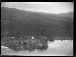 Aerial view of a coastal village with a three story stone [church?] and fale tele huts, with palm trees beyond, Apia, Western Samoa
