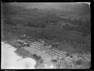 Aerial view of a coastal village with a church and neatly arranged rectangular modern [native?] housing, Apia, Western Samoa